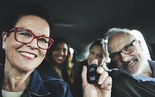 Voksen familie på fire sitter i bil