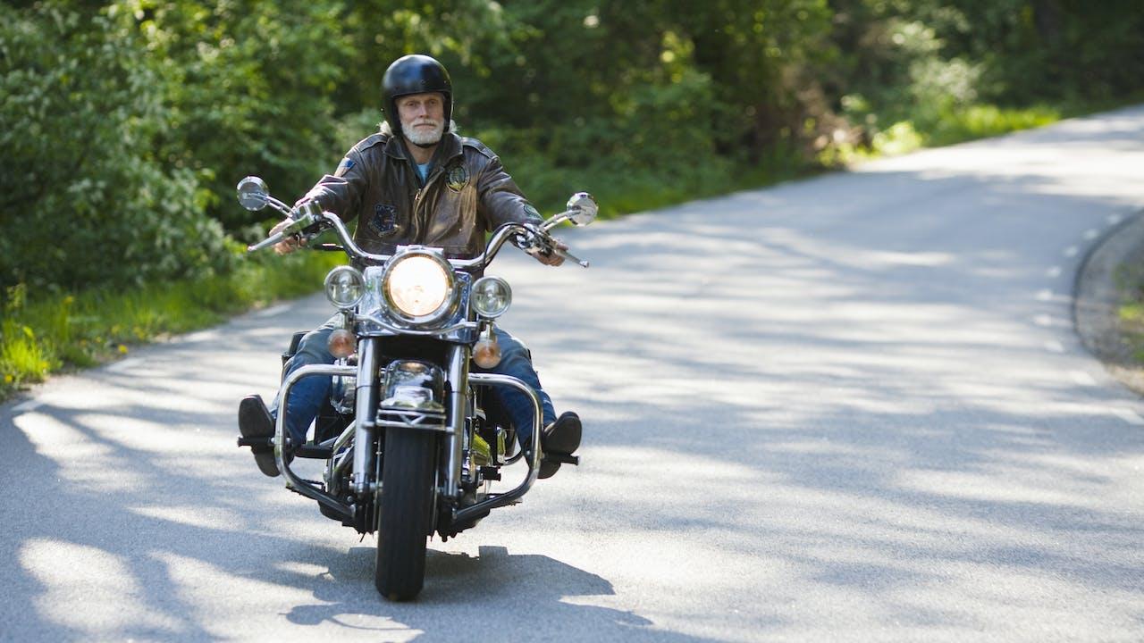 Voksen mann med skjegg kjører mkotorsykkel