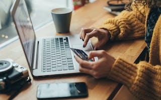 Dame foran laptop med bankkort