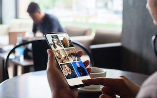 Person på kafé holder mobil i hånda
