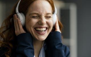 Smilende ung kvinne med hodetelefoner