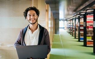 Ung mann med laptop i bibliotek