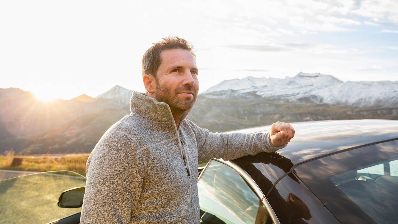 Voksen mann lener armen mot toppen av bil i fjellandskap