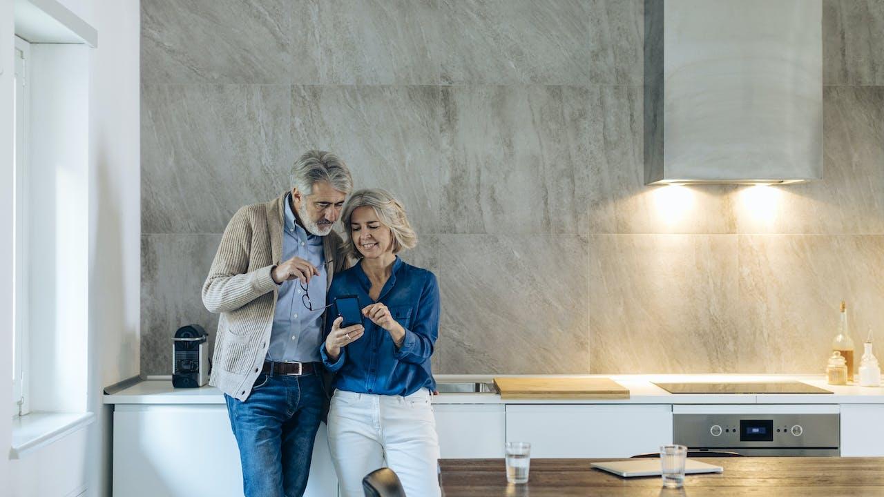 Voksent par ser på mobil på kjøkkenet