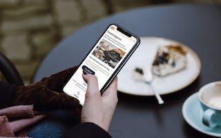 Bildet viser en hånd som holder en telefon med E24 sin Fondsvelger på displayet