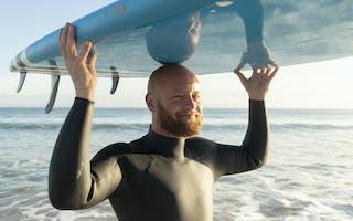 Mann med skjegg og surfebrett på hodet