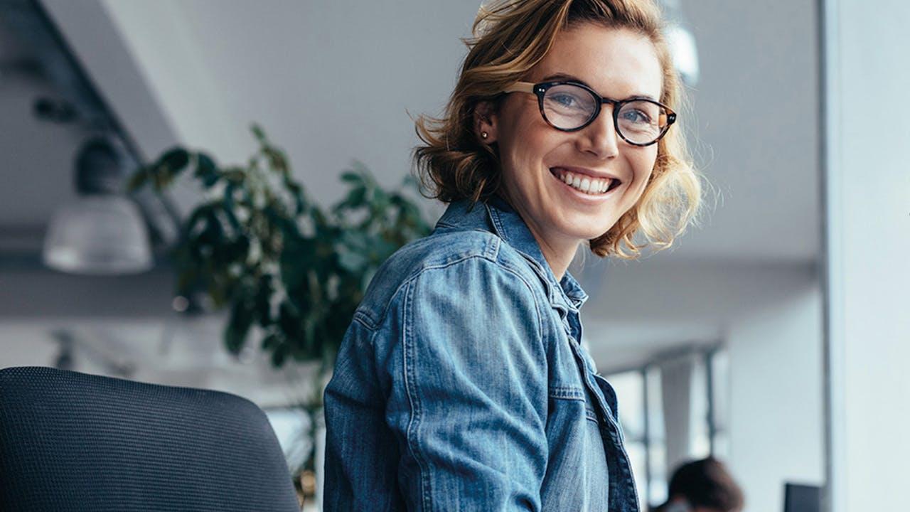 Smilende dame sitter foran datamaskin