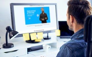 Mann ser på dataskjerm med Schibsted annonseskole