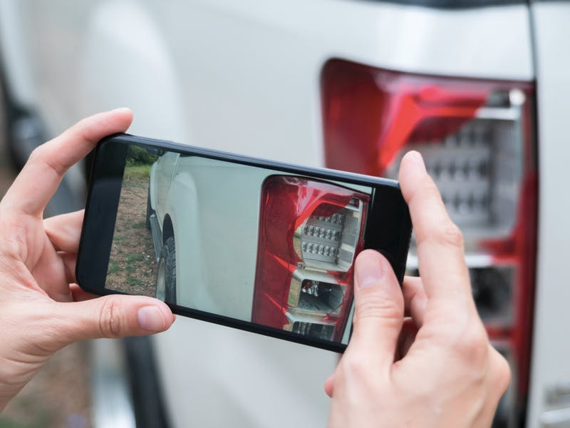 Person tar bilde av en bil med mobiltelefonen