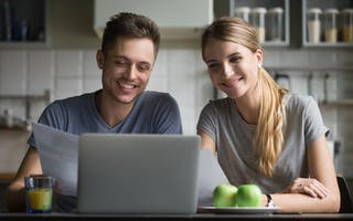 Smilende mann og dame foran laptop
