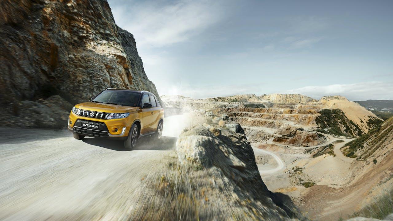 Gul bil kjører i fjellandskap