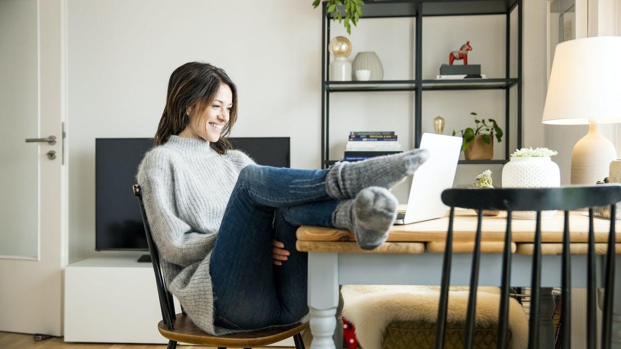 Dame med beina på bordet foran laptop