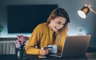 Dame med gul genser ser på laptop