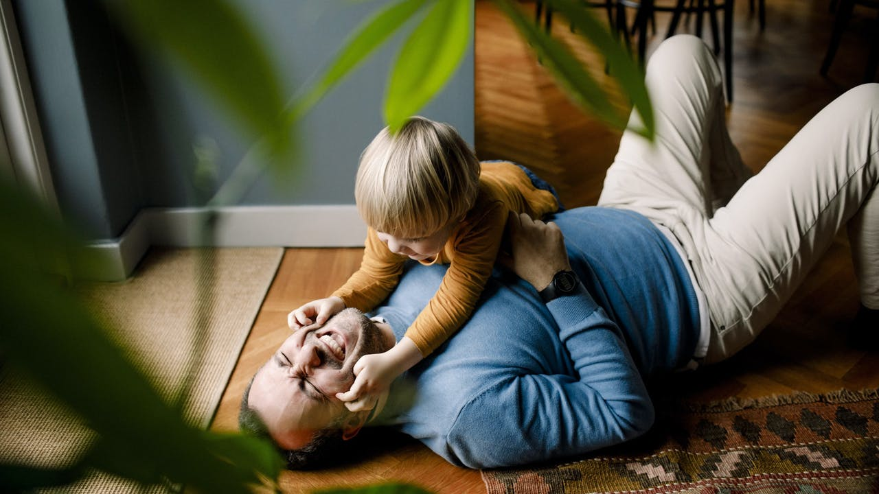 Far og sønn leker på gulvet