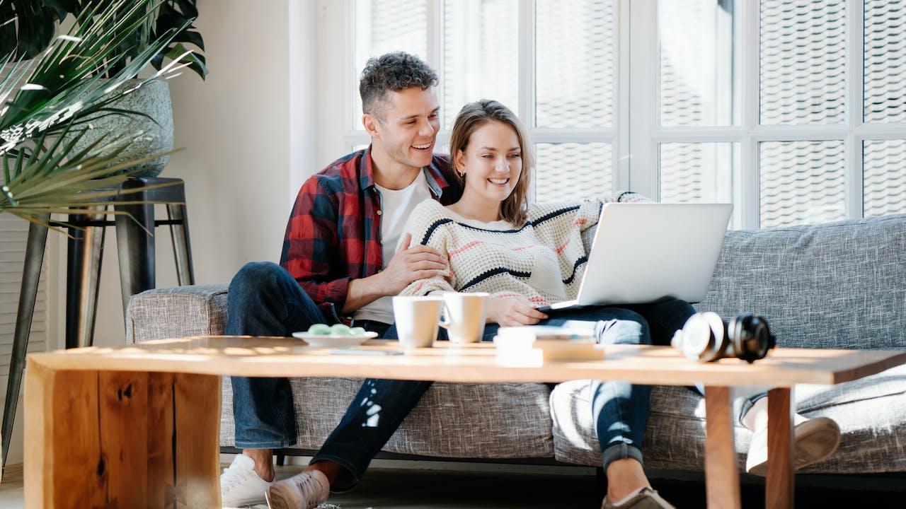 Par sitter i sofa med laptop i fanget
