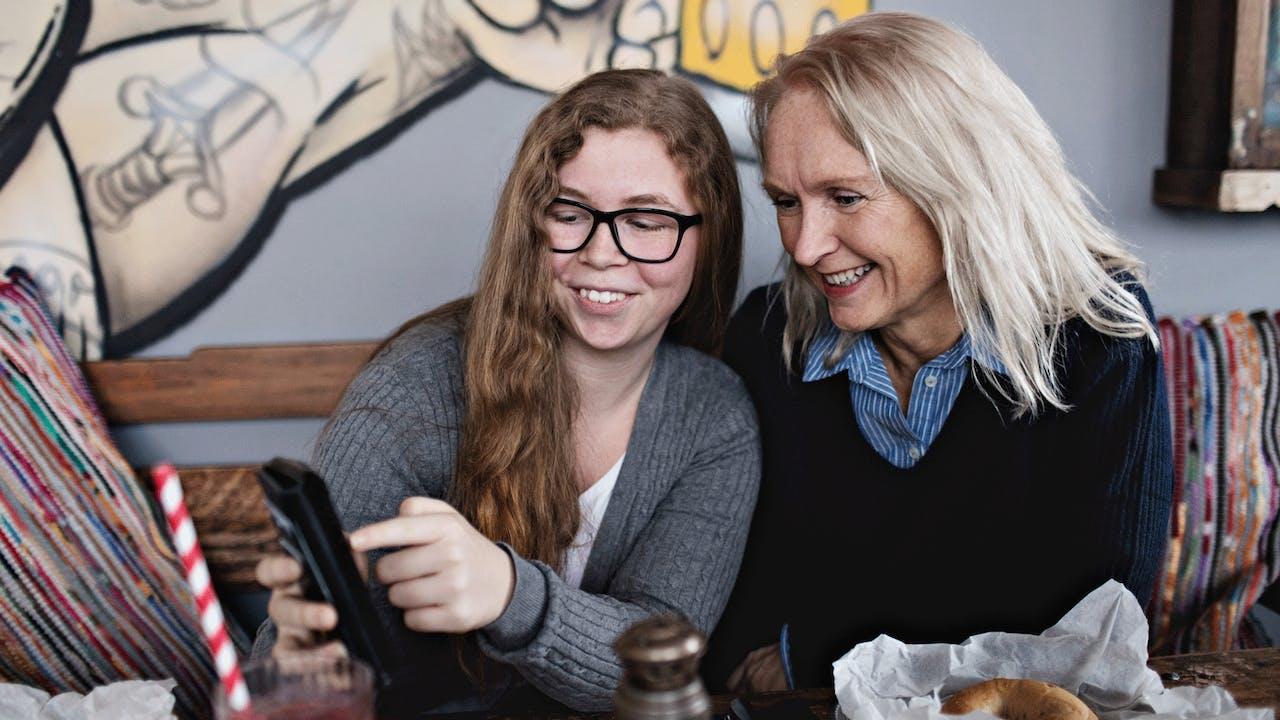 To damer ser på mobiltelefon