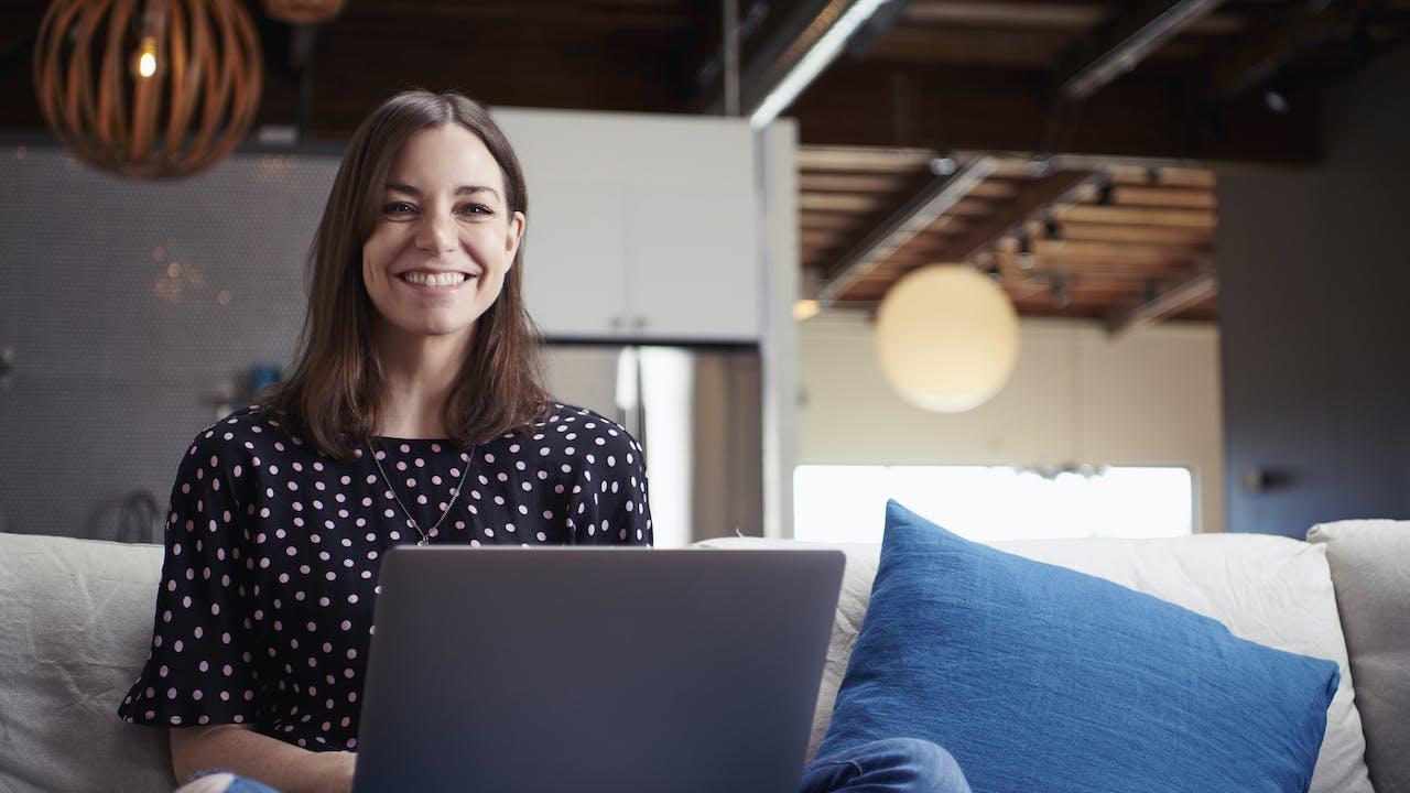 Ung kvinne sitter i sofa med laptop
