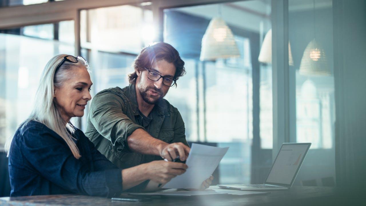 Kvinne og mann ser på papirer i kontorlandskap