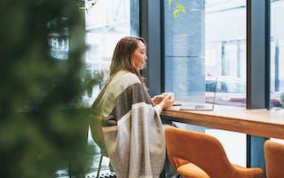 Kvinne sitter på cafe med kaffe og laptop. Ser tenkende ut.