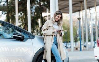 Dame står smilende ved bilen sin, mens hun ser på telefonen.