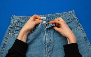 Fest nøkkelringen rundt bukseknappen.