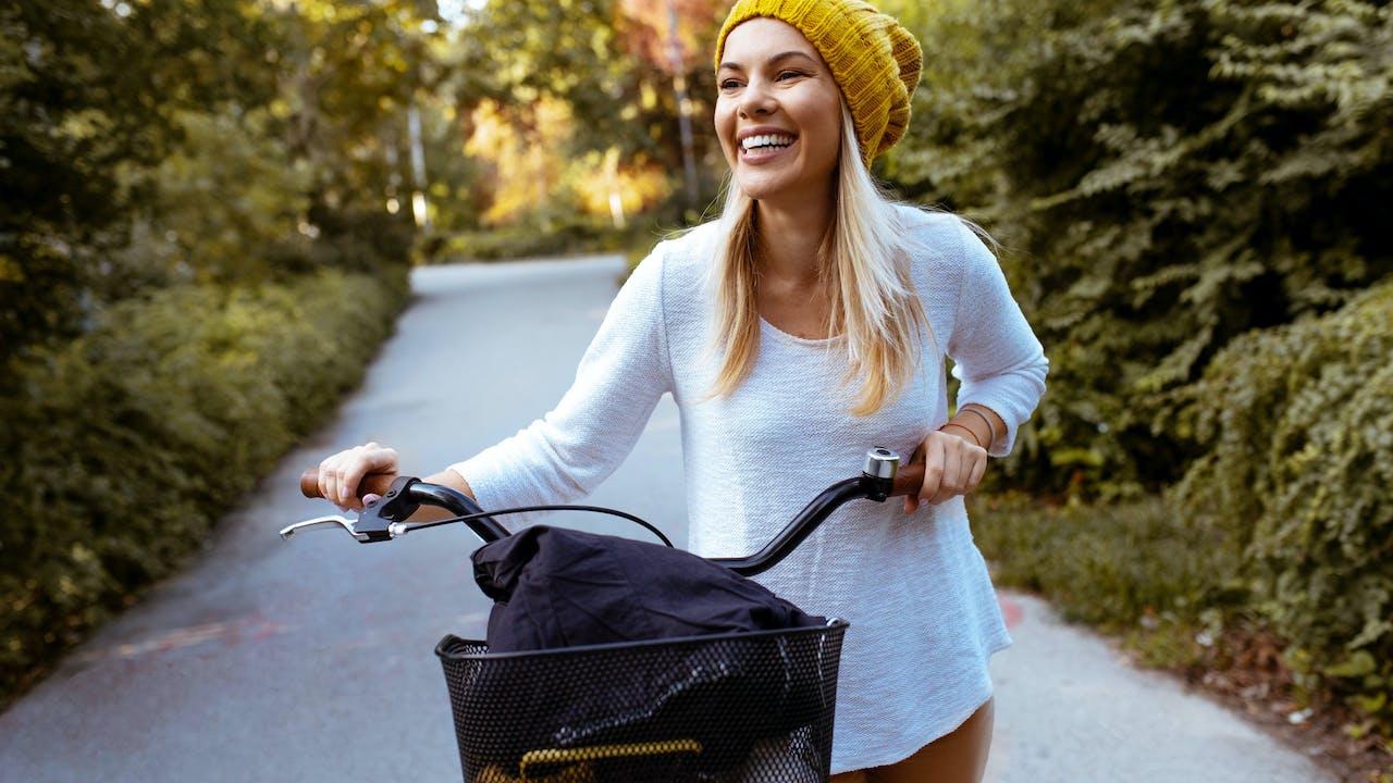 Kvinne gående med sykkel