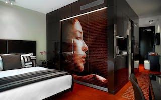 Hotell i london. bilde av dame på dodøren. stor dobbeltseng