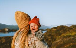 Dame holder en baby ute i naturen. Solen er på vei ned.
